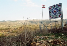 A placard and a flag in a rural landscape. Image by Walid El Houri, 2007, used with permission from the author.