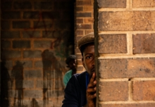 A man half hiding behind a column. Photo by Gugulethu Ndlalani, 2019